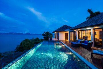 Beleuchteter Pool vor Villa über dem Meer