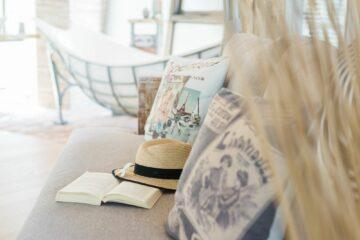 Kissen und Strohhut mit offenem Buch auf Liege