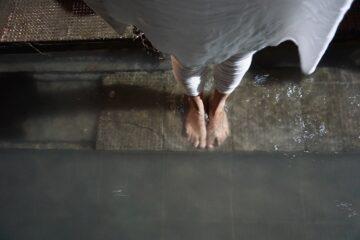 Füße von oben im Wasser fotografiert