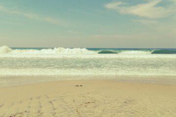 Strand und türkisblaue Wellen