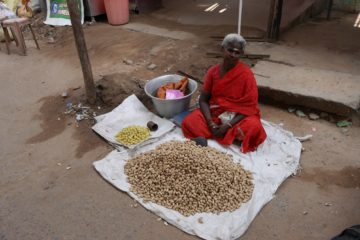 Frau sitzt vor ihrer Auslage auf dem Boden