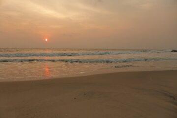 Sandstrand, Wellen und roter Sonnenuntergang
