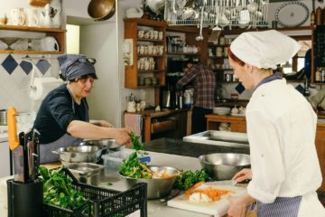 Zwei Köchinnen waschen Salat