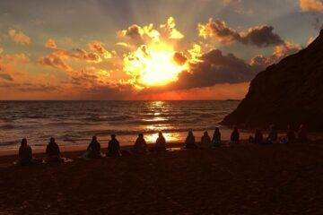 Menschen sitzen am Strand und blicken in den Sonnenuntergang