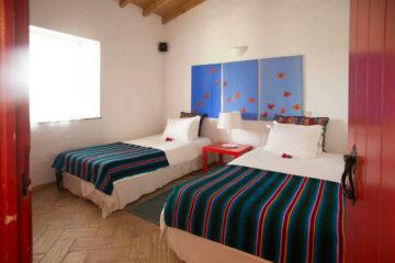 Einzelbetten mit blau-rot-gestreifter Tagesdecke