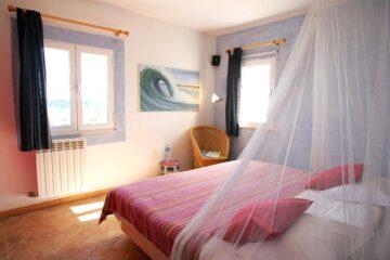 Bett mit Blick auf zwei Fenster und Stuhl