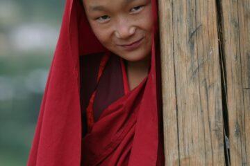 junger Mönch mit rotem Gewand lächelt schelmisch in Kamera