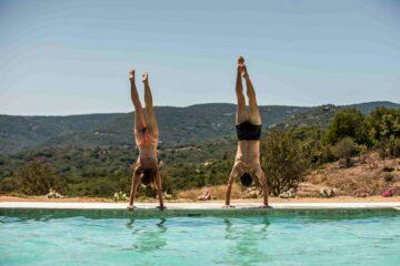 Mann und Frau machen Handstand am Rand des Pools