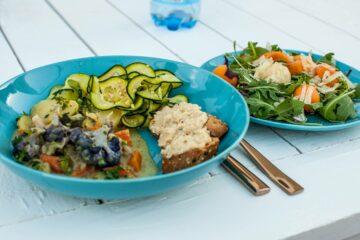 Türkiser Teller mit Salat, Blüten und Käse