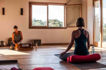 Frau sitzt im Yoga Raum bei geöffnetem Fenster