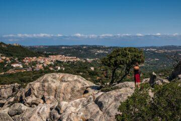 Frau steht auf Felsen und blickt ins Tal
