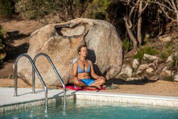 Frau lehnt am Pool an einem Stein und meditiert