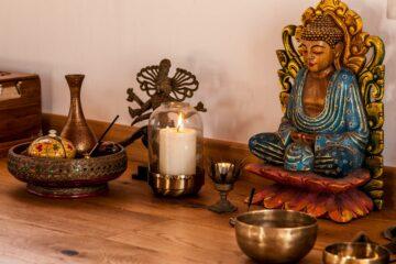 Tisch mit indischer Statue, Klangschale und Kerze