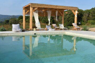 Überdachter Pavillion mit weißen Stofffbahnen am Pool