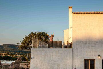 Frau breitet auf Terrasse die Arme auf