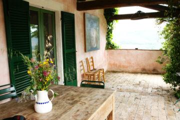 Terrasse mit grünen Fensterläden und Tisch mit frischen Blumen in Vase