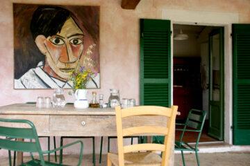 Terrasse mit Tisch, Stühlen und Bild an der Wand