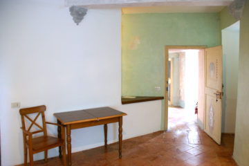 Stuhl und Tisch in weiß-türkis getünchtem Zimmer
