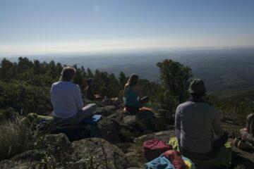 Gruppe sitzt auf Hügel mit Blick auf das Meer