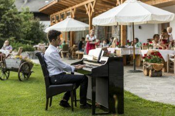 Mann spielt Klavier im Garten