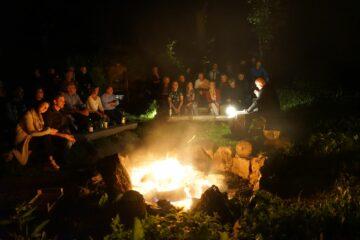 Gruppe sitzt um Feuer, Mann liest vor