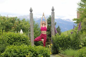 Yogini im pinken Yoga-Dress mit Sonnengrußpose