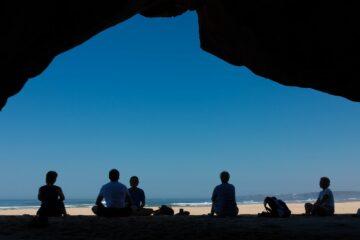 Gruppe sitzt im Schatten einer Klippe am Strand