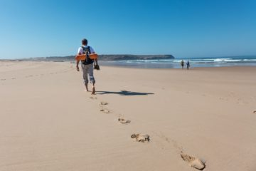 Mann wandert am Strand entlang