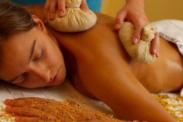 Frau liegt auf Rücken mit Kräuterstempelkissen