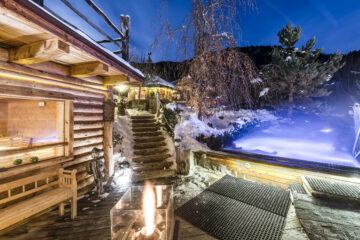 Sauna und Außenpool beleuchtet in Winterkulisse
