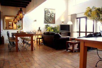 Fliesenboden mit schwarzer Couch und silbernem Kunstbild