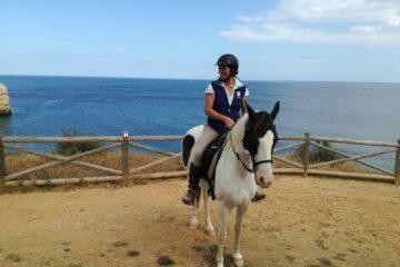 Frau sitzt auf Pferd vor Meer