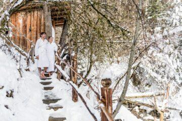 Paar steht im Bademantel vor Hütte in winterlicher Landschaft