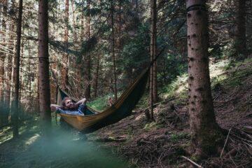 Mann in Hängematte im Wald