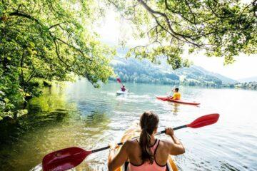 Drei Personen paddeln im Kanu auf See