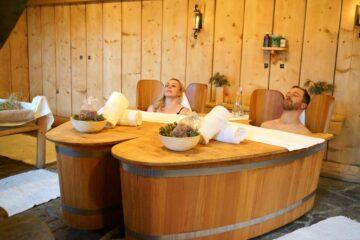 Paar liegt in Holzzubern und entspannt