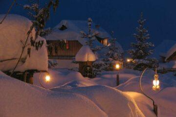 Verschneite Dächer und leuchtende Hängelampen