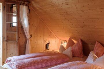 Doppelbett mit rot-weiß-karierter Bettwäsche