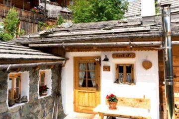 Außenansicht Almbungalow mit Holzdach und Steinen