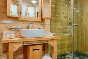 Badezimmer mit Dusche und Waschtisch in Holz
