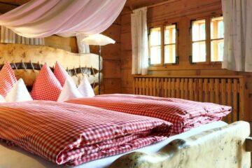 Bett mit rot-kariertem Bettbezug und Bücherregal über dem Fenster