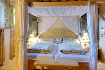 Bett in Himmelbettoptik und Holzdecke