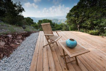 Holzterrasse mit Tisch, Stuhl und türkisem Windlicht