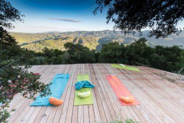 Yogamatten und Kissen auf Terrasse mit weitem Blick über Hügel