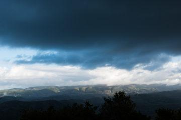 Wolkenhimmel und grüne Hügelberge im Kontrast