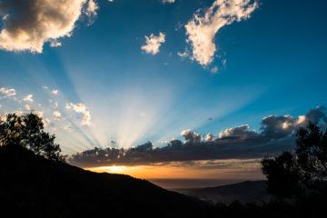 Sonne strahlt in den blauen Himmel durch Wolke