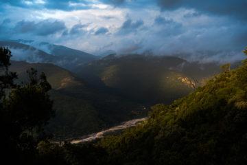 Sonne bricht durch Wolken über grünen Hügeln