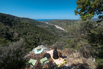 Frau sitzt auf Yogamatte und schuat ins Tal