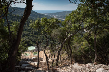 Blick auf kleine Terrasse mit Tisch und zwei Stühlen mitten in den Hügeln zwischen Bäumen