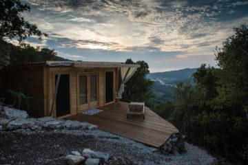 Bungalow aus Holz mit Terrasse und Liege hoch über den Hügeln